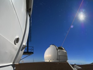 In this view from the Keck Observatory rooftop, the Keck II Laser Guide Star probes the sky as a waxing moon ascends above the summit of Mauna Kea.